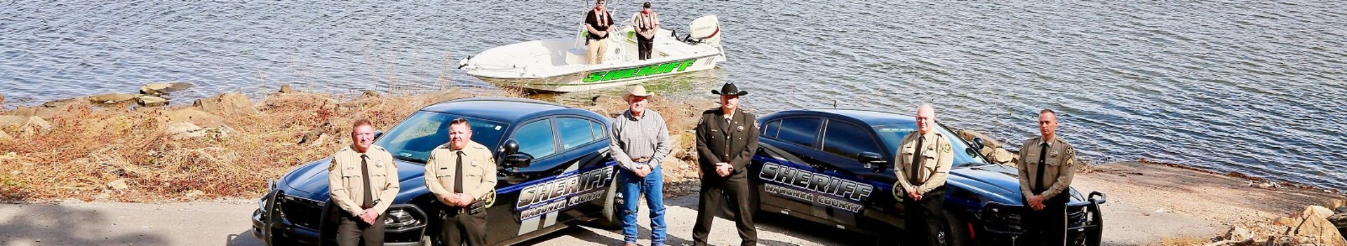 Wagoner County Sheriff's Office employees standing in front of patrol cars and boat